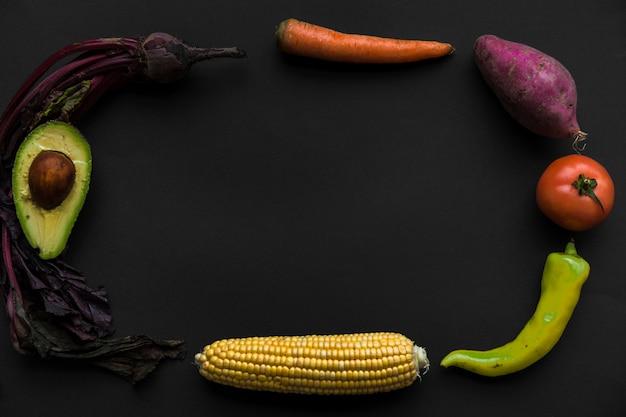 Diferentes tipos de alimentos crudos saludables formando marco sobre fondo negro