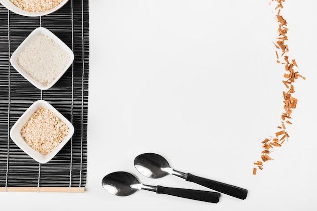 Diferentes tipos de arroz crudo en mantel con palitos de canela y cuchara sobre fondo blanco