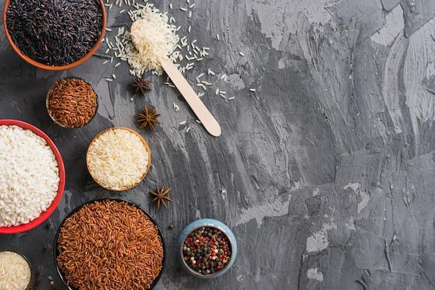 Diferentes tipos de arroz crudo en tazón y especias secas sobre papel tapiz texturizado