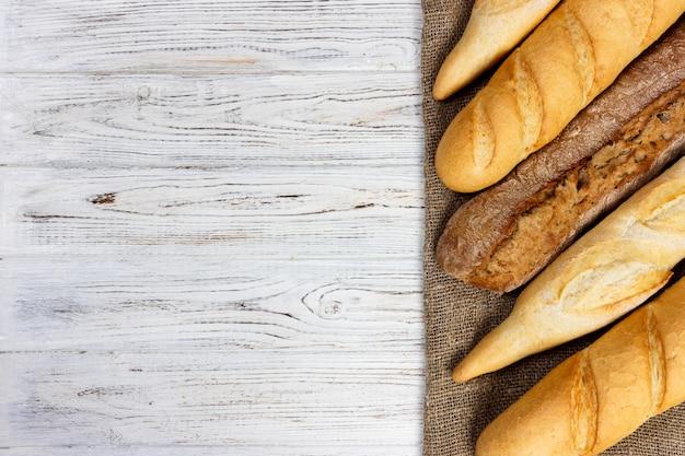 Diferentes tipos de baguette en un fondo de madera copyspace