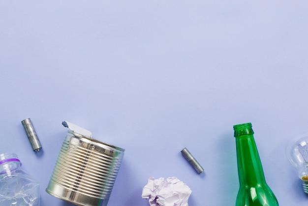 Diferentes tipos de basura para el reciclaje sobre fondo azul
