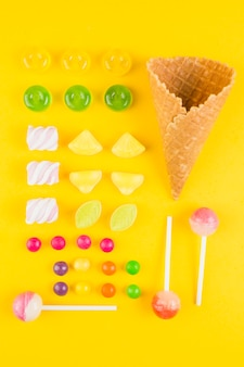 Diferentes tipos de caramelos y cono de waffle de helado sobre fondo amarillo