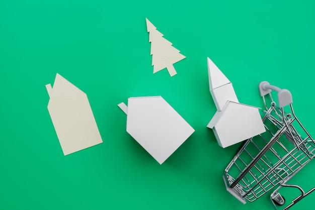 Diferentes tipos de casas de papel; árbol que cae del carro de compras sobre fondo verde
