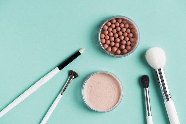 Diferentes tipos de cepillos con perlas compactas y bronceadas sobre fondo verde