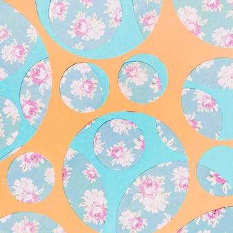 Diferentes tipos de círculos geométricos sobre el papel tapiz floral.