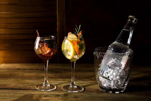 Diferentes tipos de cócteles a base de whisky con cubeta de hielo de vidrio sobre fondo de madera oscura