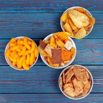 Diferentes tipos de comida chatarra, palitos salados, galletas saladas en la mesa de madera