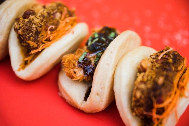 Diferentes tipos de comida tradicional de taiwán gua bao sobre fondo rojo