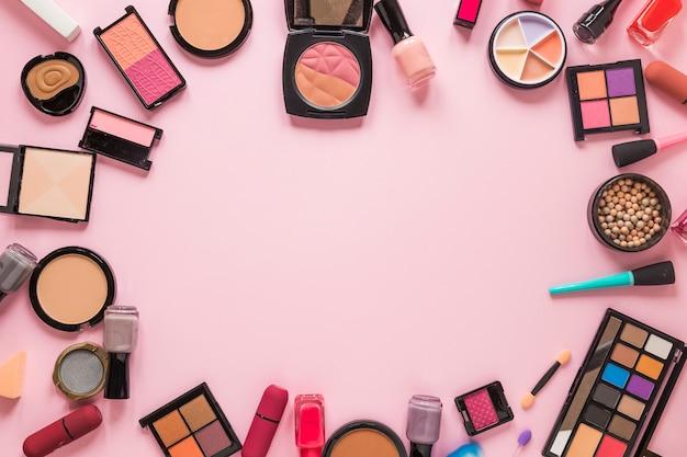 Diferentes tipos de cosméticos esparcidos sobre mesa rosa.