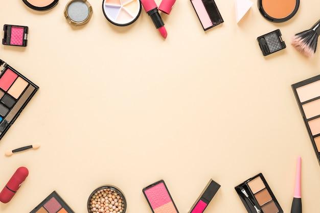 Diferentes tipos de cosméticos esparcidos sobre tabla beige.