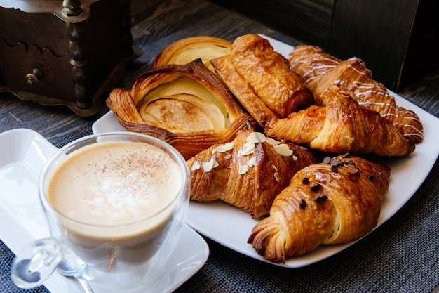 Diferentes tipos de croissants con café en la mesa