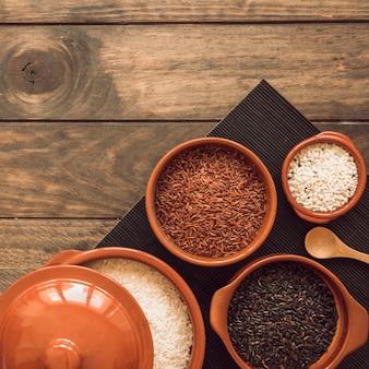 Diferentes tipos de cuencos de granos de arroz en mantel sobre la mesa de madera