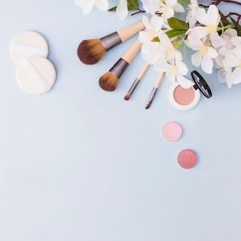 Diferentes tipos de pinceles de maquillaje; esponja; sombra de ojos y colorete con flores blancas sobre fondo azul