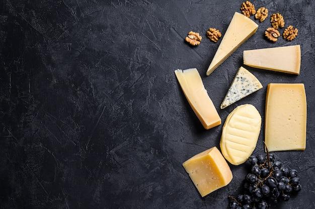 Diferentes tipos de deliciosos quesos. fondo negro. vista superior. espacio para texto