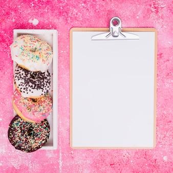 Diferentes tipos de donuts en una caja rectangular blanca cerca del portapapeles con papel blanco sobre fondo rosa