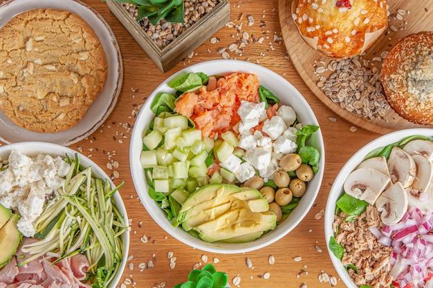 Diferentes tipos de ensalada y postre en mesa de madera.