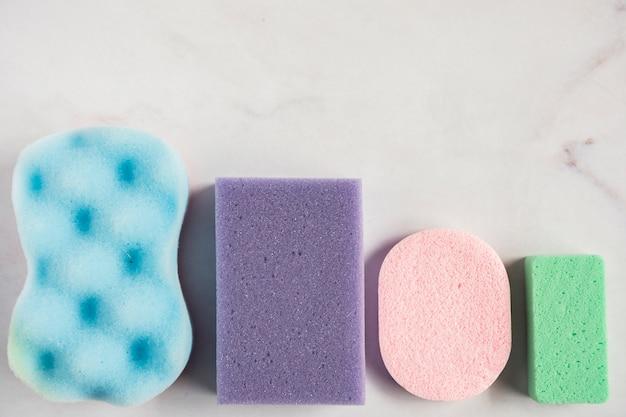 Diferentes tipos de esponja colorida y de forma aislada sobre fondo blanco