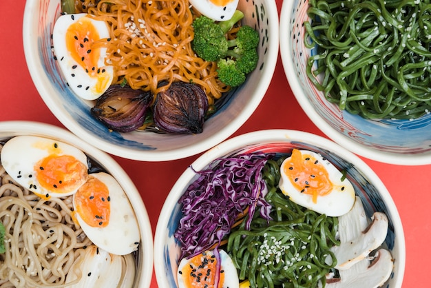 Diferentes tipos de fideos con huevos; algas y ensalada en el tazón sobre fondo rojo