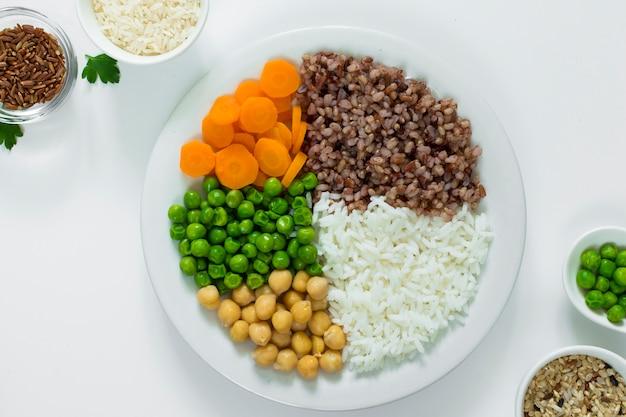 Diferentes tipos de gachas de avena con verduras en un plato con tazones de arroz en la mesa