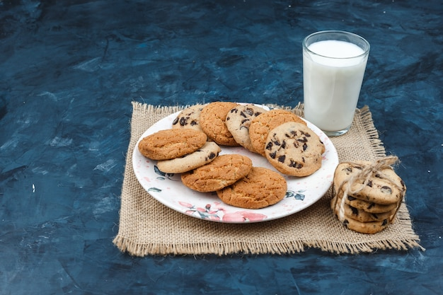 Diferentes tipos de galletas, leche en un mantel sobre un fondo azul oscuro. vista de ángulo alto.