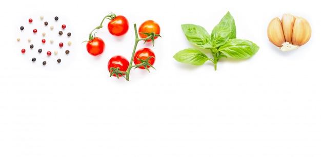 Diferentes tipos de granos de pimienta, tomates cherry frescos, hojas de albahaca y ajo sobre fondo blanco.
