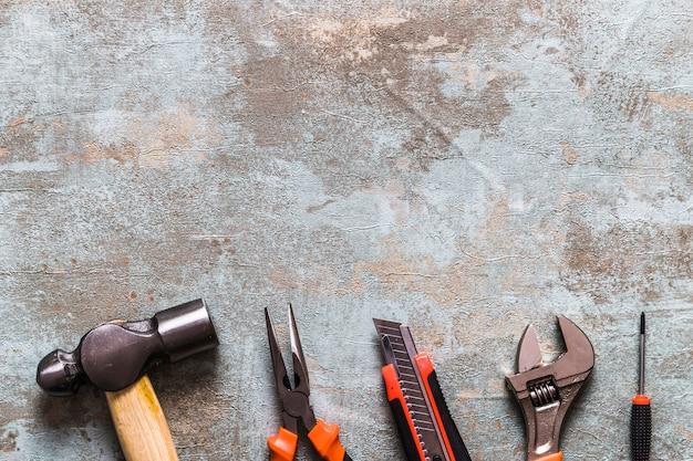 Diferentes tipos de herramientas de trabajo dispuestos en una fila en el escritorio de madera oxidado