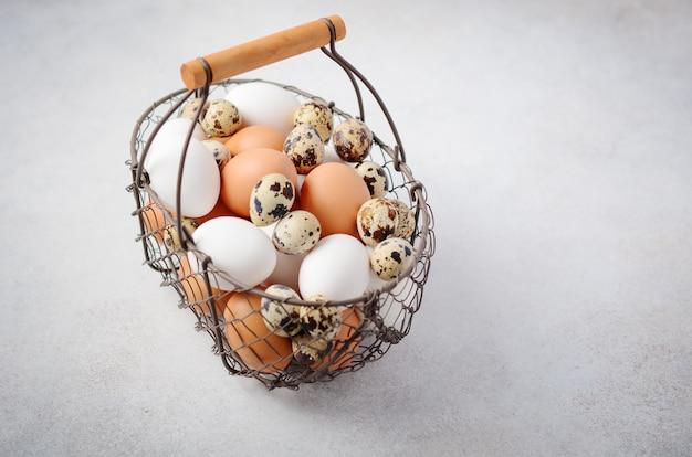 Diferentes tipos de huevos en una canasta sobre una mesa de concreto gris