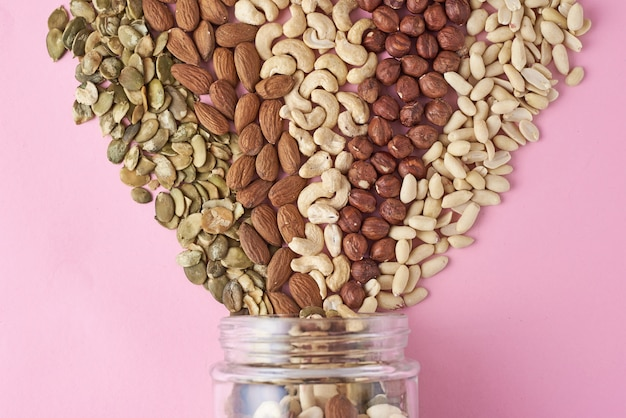 Diferentes tipos de nueces y semillas en un frasco de vidrio sobre fondo rosa