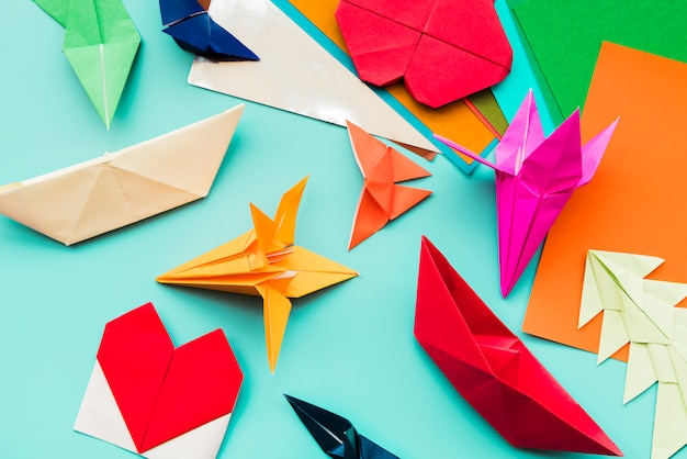 Diferentes tipos de origami de papel de colores sobre fondo verde azulado