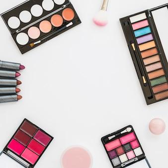 Diferentes tipos de paleta de maquillaje de colores con pintalabios; esponja y polvo compacto sobre fondo blanco.