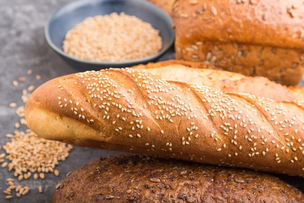 Diferentes tipos de pan recién horneado sobre una superficie de hormigón negro. vista lateral, enfoque selectivo.