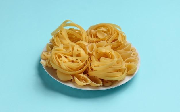 Diferentes tipos de pasta italiana cruda en placa sobre fondo azul.