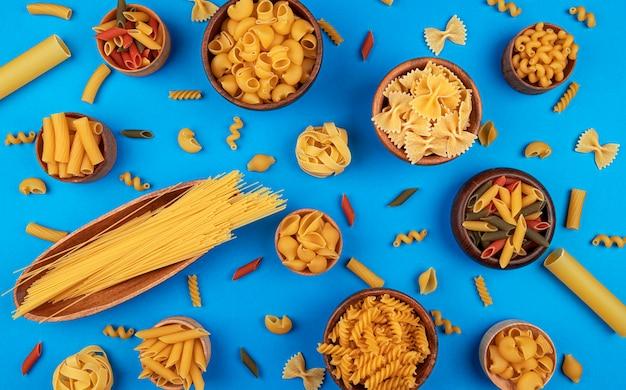 Diferentes tipos de pasta sobre fondo azul con espacio para copiar texto, composición plana del concepto de ingredientes de comida italiana, vista superior del patrón de pasta mixta seca en la tabla de colores