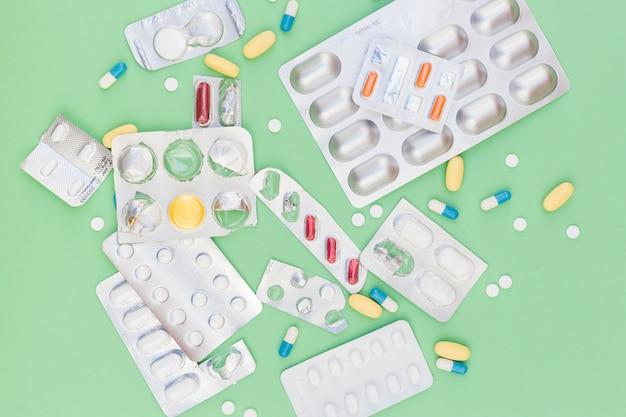 Diferentes tipos de píldoras médicas en blíster con fondo verde