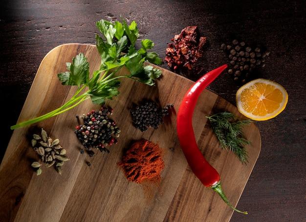 Diferentes tipos de pimiento, cardamomo, rodaja de limón y hojas de apio sobre un fondo de madera