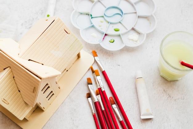 Diferentes tipos de pincel; modelo de la casa y paleta de colores y tubo de pintura acrílica sobre fondo blanco con textura