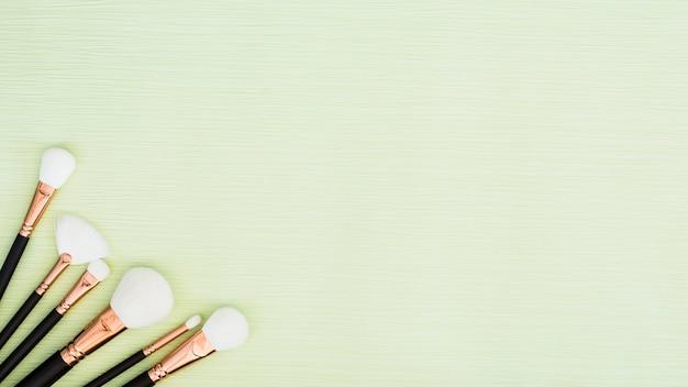 Diferentes tipos de pinceles de maquillaje blanco en la esquina del fondo de menta verde