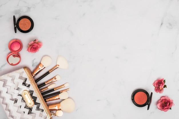Diferentes tipos de pinceles de maquillaje en la bolsa con polvos faciales compactos y flores color de rosa sobre fondo blanco