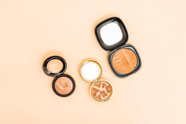 Diferentes tipos de polvos compactos para la cara sobre fondo beige