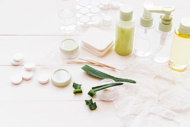 Diferentes tipos de productos de cosmética natural en mesa de madera blanca.