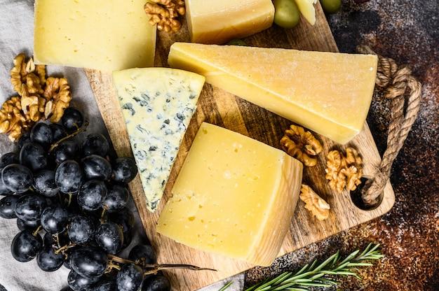 Diferentes tipos de queso, aceitunas y romero. surtido de deliciosos aperitivos. fondo oscuro vista superior