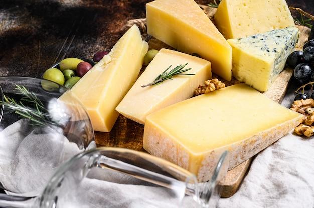 Diferentes tipos de queso, aceitunas y romero. surtido de deliciosos aperitivos. vista superior