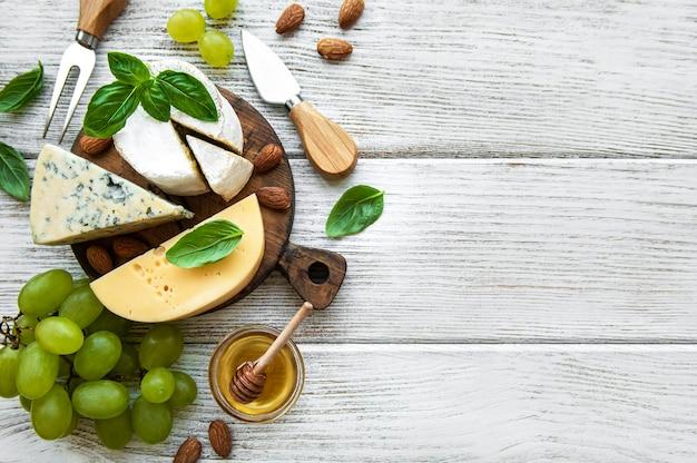 Diferentes tipos de queso con bocadillos en una mesa de madera vieja blanca