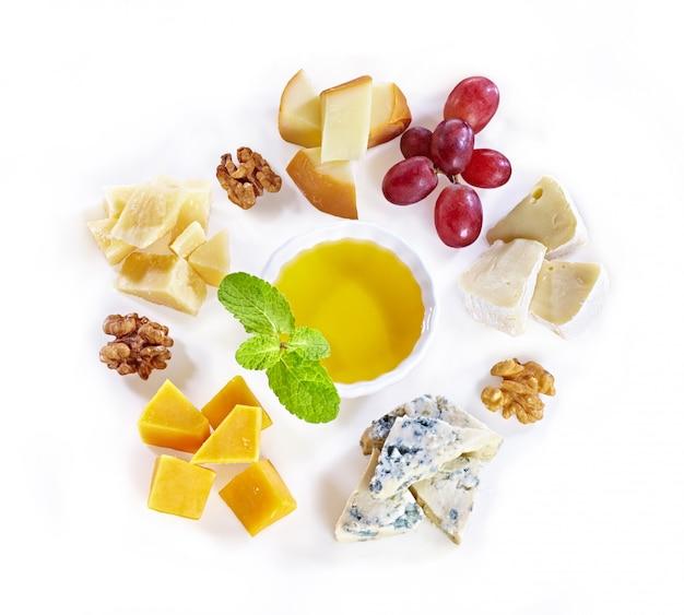 Diferentes tipos de queso con miel, uva, nueces sobre fondo blanco. vista superior. rebanadas de queso azul, queso cheddar, parmesano, maasdam y queso brie