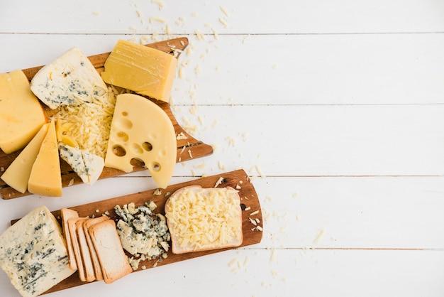 Diferentes tipos de queso con rebanadas de pan en una tabla de cortar sobre un escritorio blanco