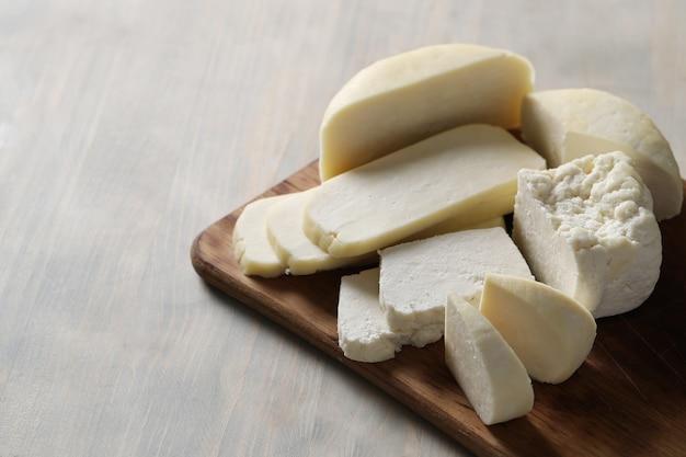 Diferentes tipos de queso en tabla de cortar.