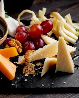 Diferentes tipos de queso con uva y nueces.