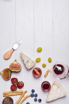 Diferentes tipos de quesos con copa de vino y frutas.