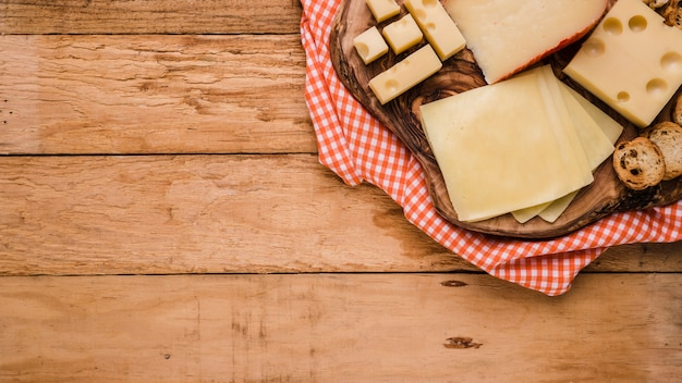 Diferentes tipos de quesos en montaña de madera con mantel sobre banco