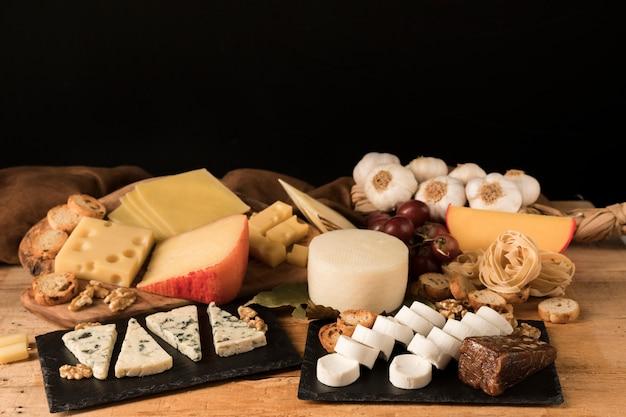 Diferentes tipos de quesos organizan en piedra pizarra en mesa de madera.